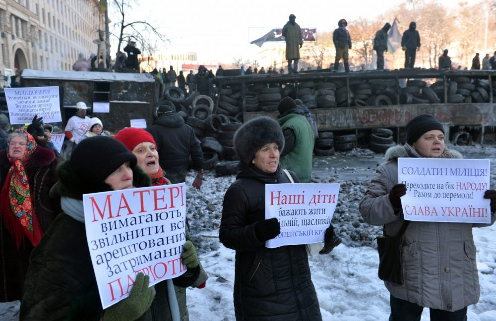 Women hold placards calling police to stop blood-letting and join protesters as they stay in front of the police line in Kiev on January 24, 2014. (Sergei Supinsky/AFP/Getty Images)