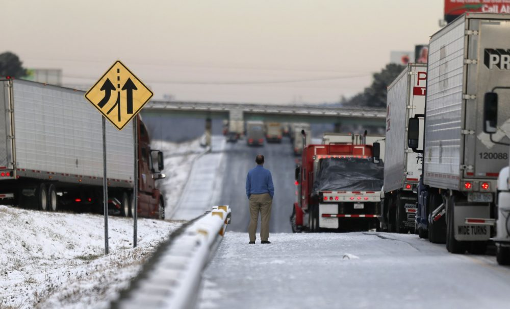 A man stands on the frozen roadway as he waits for traffic to clear along Interstate 75 Wednesday, Jan. 29, 2014, in Macon, Ga. (John Bazemore/AP)