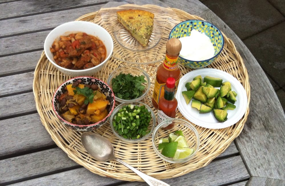 Two different chilis made by Kathy Gunst, along with cornbread, garnishes and hot sauces are pictured. (Qainat Khan/Here & Now)