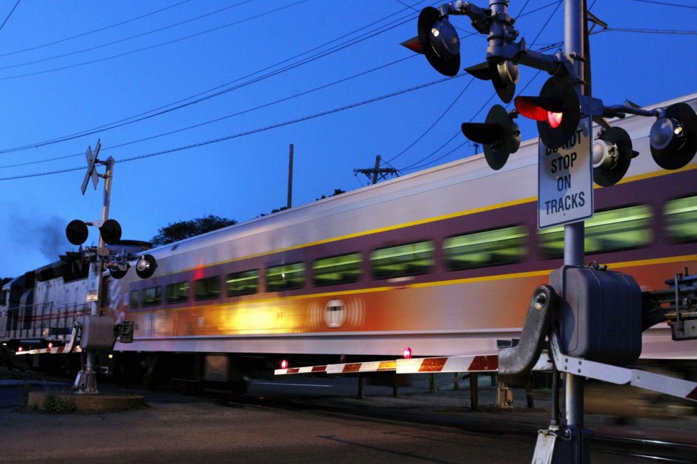A commuter train passes crossing gates as it leaves the MBTA station in Andover, Mass. (AP)