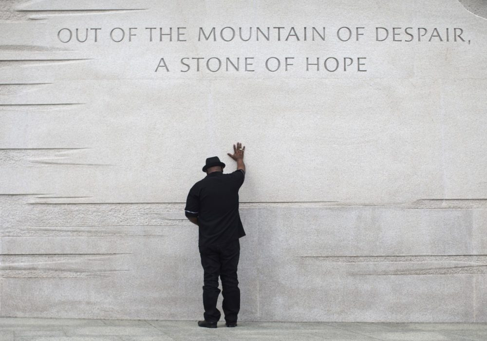 Rev. Bobby Turner or Columbus, Ohio, places his hand on the Martin Luther King Jr. Memorial, Thursday, Aug. 22, 2013, in Washington. (AP)