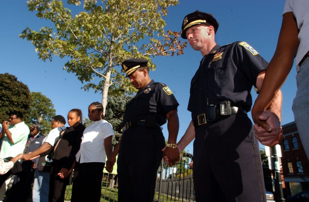 Massachusetts Bay Transportation Authority Chief Joseph Carter, center, and Boston police Superintendent of the Bureau of Investigative Services Paul Joyce, right, join hands in prayer, Sunday, Sept. 26, 2004 in the Dorchester neighborhood of Boston, for families that have lost youth to street violence.
