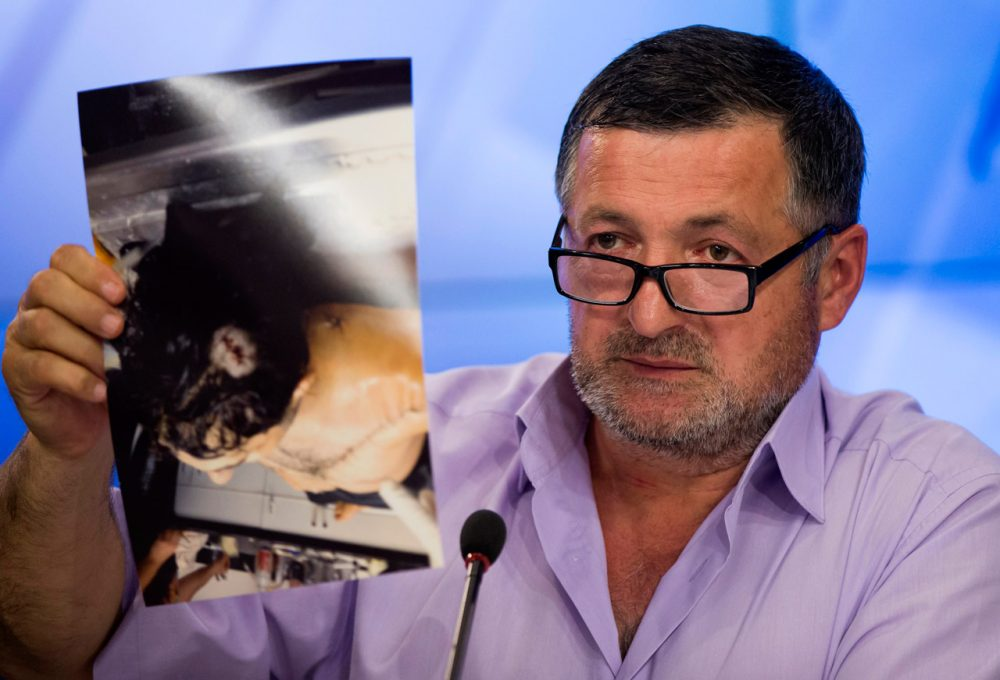 "Abdul-Baki Todashev holds a photo he claims is of his dead son, Ibragim, during a news conference in Moscow, Russia, on May 30, 2013. The father, who says agents killed his son ""execution style,"" showed journalists 16 photographs of Ibragim in the morgue with what he said were six gunshot wounds to his torso and one to the back of the head. (Alexander Zemlianichenko/AP)"