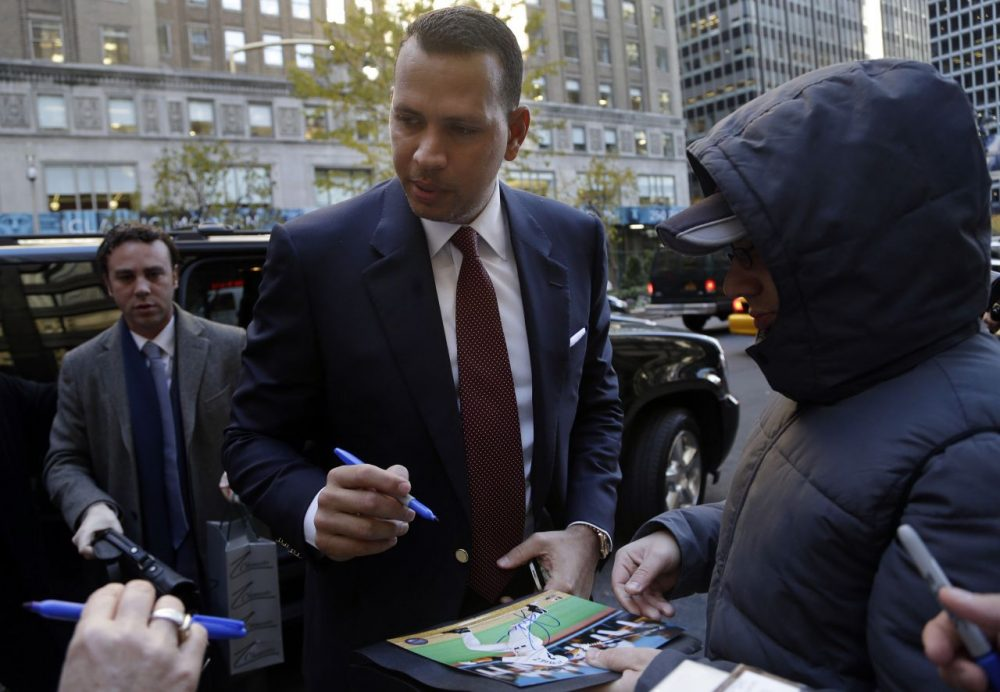 Alex Rodriguez signs autographs as he arrives at MLB headquarters in New York. (Seth Wenig/AP)