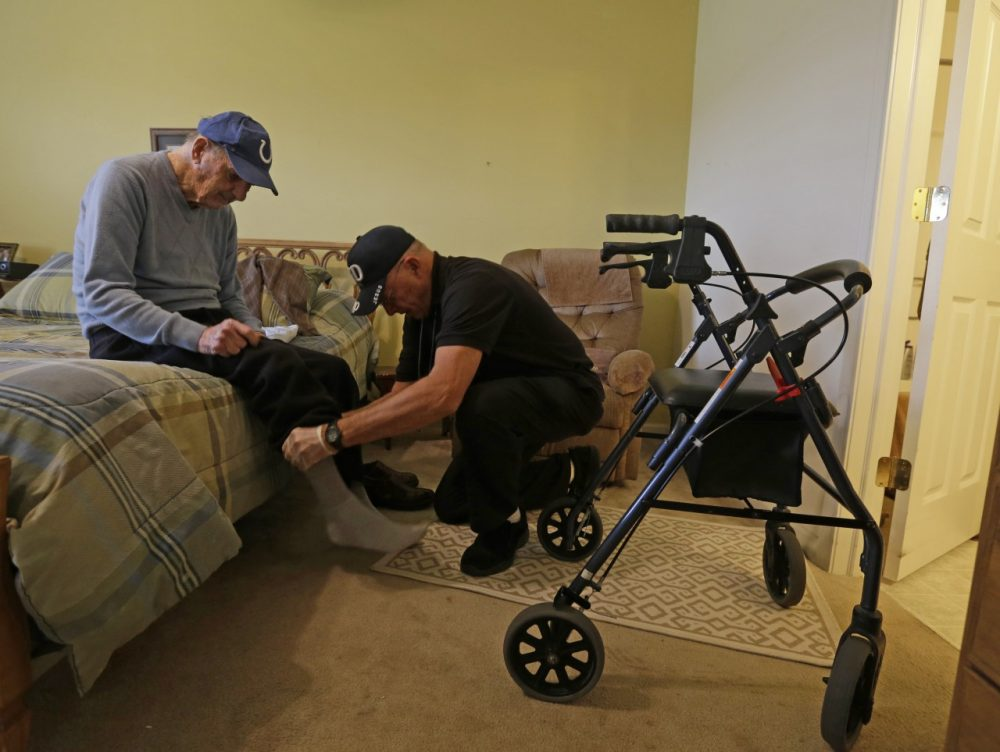 Caregiver Warren Manchess helps Paul Gregoline with his shoes and socks, in Noblesville, Ind. (Darron Cummings/AP)