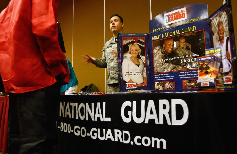A National Guard recruiter speaks to a potential soldier at a career fair December 8, 2009 in Denver, Colorado. (John Moore/Getty Images)