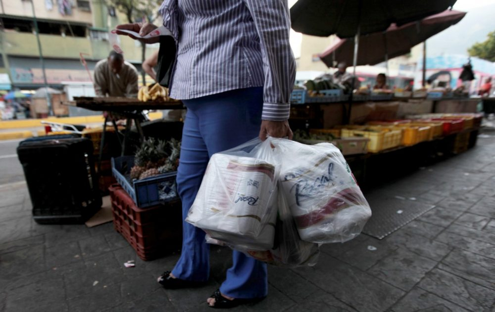 A woman who just bought toilet paper at a grocery store reads her receipt as she leaves the private store in Caracas, Venezuela, Wednesday, May 15, 2013. First milk, butter, coffee and cornmeal ran short. Now Venezuela is running out of the most basic of necessities _ toilet paper. Economists say Venezuela's shortages stem from price controls meant to make basic goods available to the poorest parts of society and the government's controls on foreign currency. (Fernando Llano/AP)