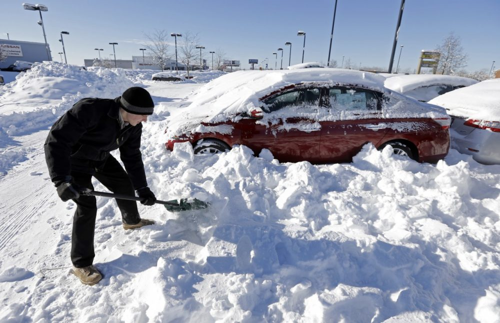 A car salesmen digs out cars covered in snow at a dealership in Indianapolis, Jan. 7, 2014, as temperatures hovered around zero. (Michael Conroy/AP)