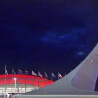 In this Feb. 1, 2014 photo, the roof of the Bolshoy Ice Dome is lit in red as the Olympic cauldron stands at right in the Olympic Park before the start of the 2014 Winter Olympics in Sochi, Russia. (David Goldman/AP)