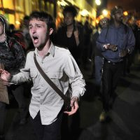 """Demonstrators with """"Occupy Boston"""" march toward the police station where fellow demonstrators were brought after police arrested people sleeping in an expansion of the Occupy Boston tent village in Boston, in the early morning hours of Tuesday, Oct. 11, 2011. (Josh Reynolds/AP)"""