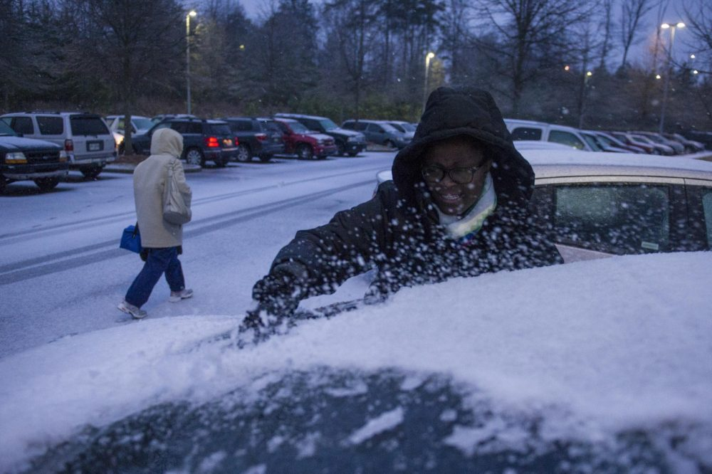 Shmetrice Moore, a nurse at an Emory hospital, scrapes snow and ice off her windshield as she and others are released early from their shift before a winter storm on Wednesday, Feb. 12, 2014, in Johns Creek, Ga. (John Amis/AP)