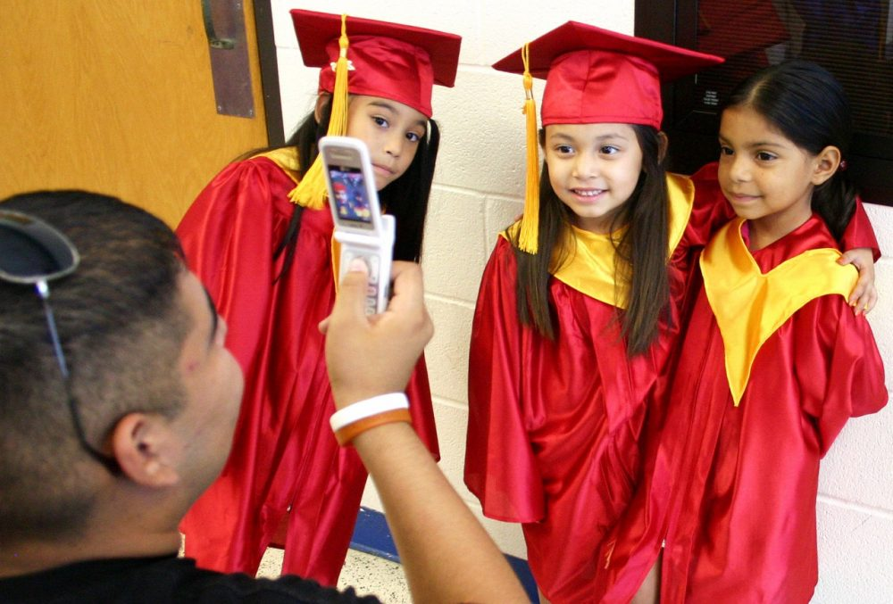 David Gonzales takes a photo of Denycia Rubio, Haley Santana Gonzales and Jackie Guillen before their graduation from a headstart graduation ceremony for four-year-old pre-K students. (Lynn Hermosa/AP)