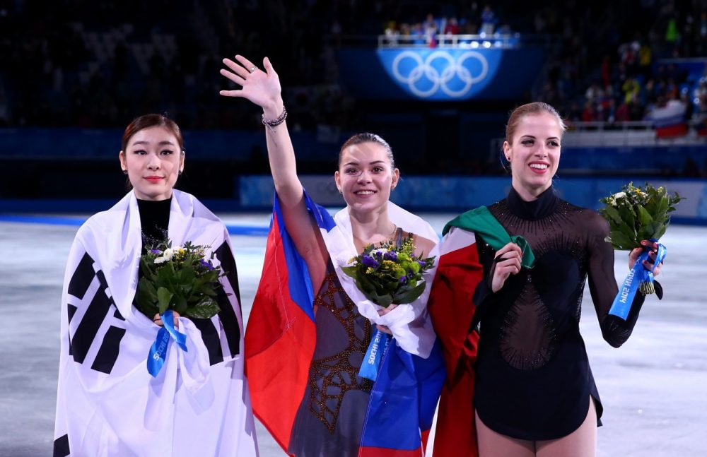 From left to right, silver medalist Yuna Kim of South Korea, gold medalist Adelina Sotnikova of Russia and bronze medalist Carolina Kostner of Italy celebrate during the flower ceremony for the Ladies' Figure Skating. (Ryan Pierse/Getty Images)