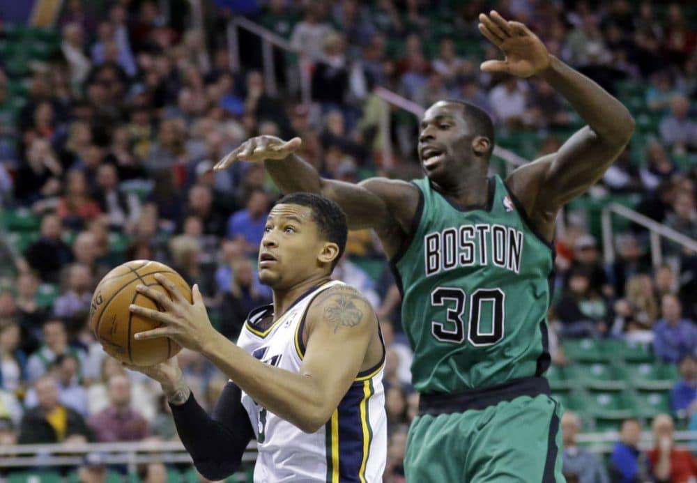 Utah Jazz's Trey Burke, left, goes to the basket as Boston Celtics' Brandon Bass (30).(AP/Rick Bowmer)