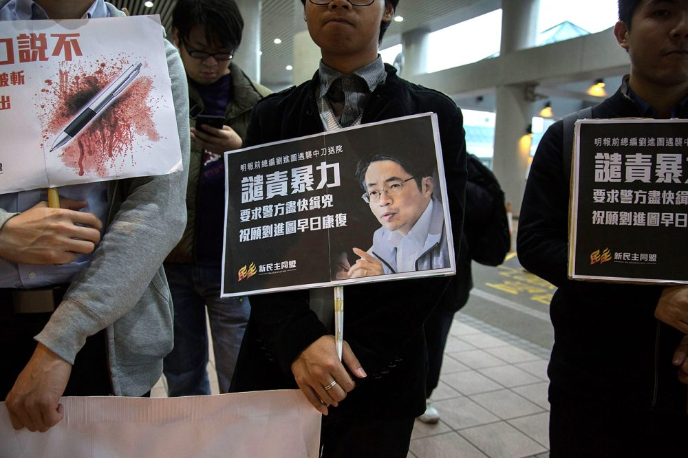Pro-democracy activists hold a sign with an image of former chief editor of the Ming Pao daily Kevin Lau Chun-to as they attend a candlelight vigil at a hospital, to urge the police to solve the stabbing incident involving Lau, on February 26, 2014 in Hong Kong. (Lam Yik Fei/Getty Images)