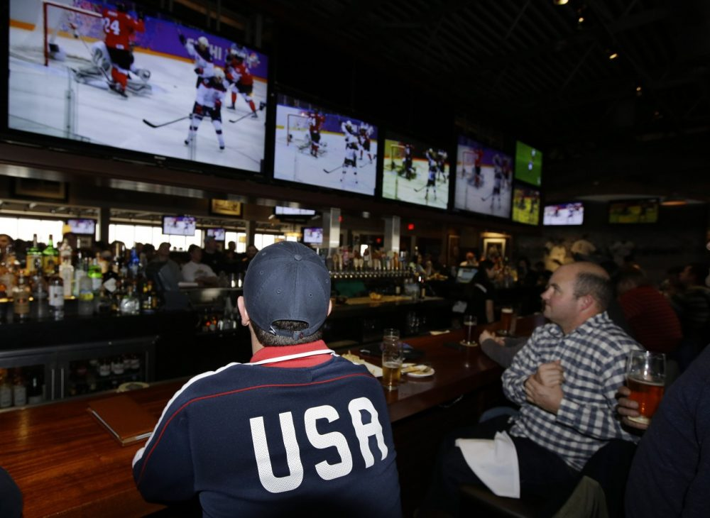 Jason Bryer, left, and Jeremy Pafundi watches the USA play Canada in a Sochi Olympics semifinal match at the Cask 'n Flagon Restaurant and Sports Bar in Marshfield, Mass., Friday, Feb. 21, 2014. (AP)