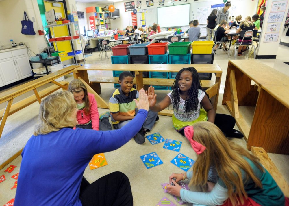 Third-grade teacher Sherry Frangia, left, high-fives student Jayla Hopkins during a math lesson at Silver Lake Elementary School in Middletown, Del. Tuesday, Oct. 1, 2013. Silver Lake has begun implementing the national Common Core State Standards for academics. (AP)