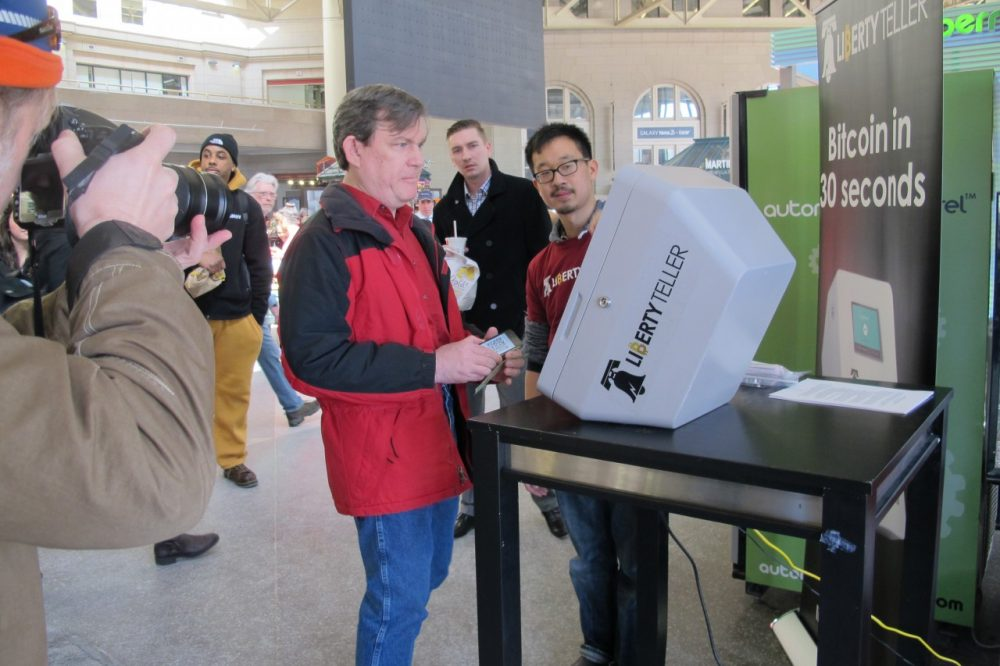 Paul Watts of Newton tries out the bitcoin kiosk at South Station while Liberty Teller co-founder Chris Yin helps. (Anna Taylor/WBUR)