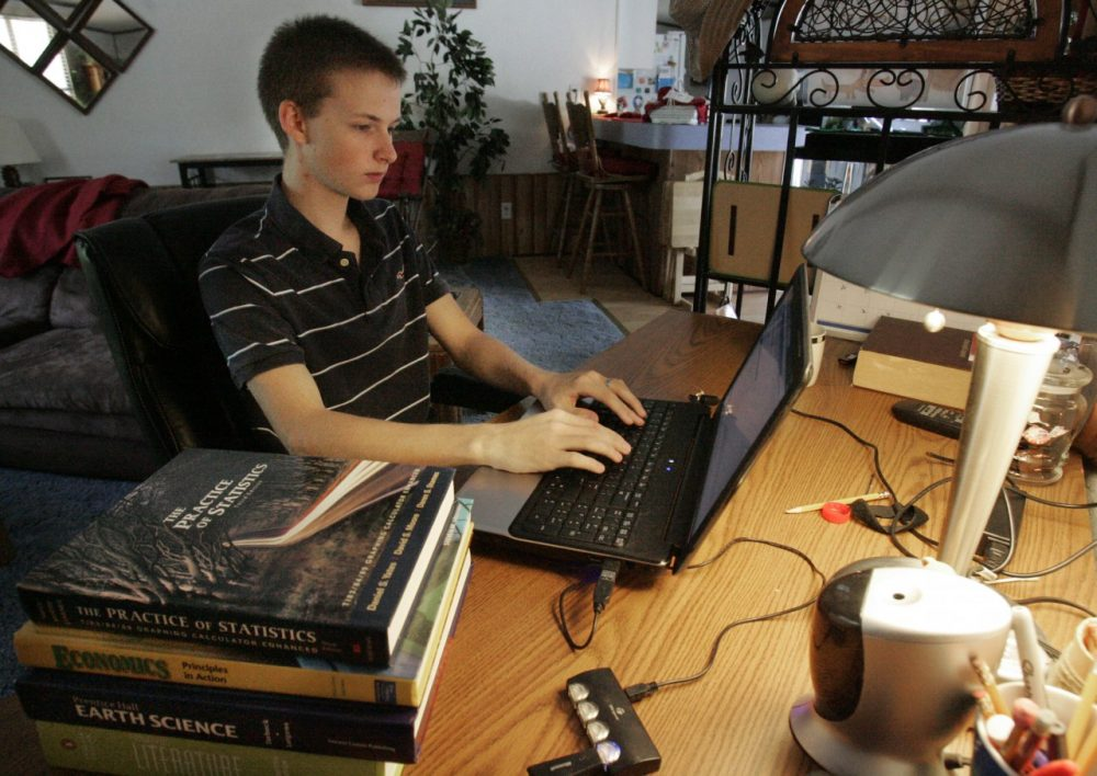 Jared Dennis, 18, logs onto his school website in his home in Lexington, S.C. (AP/Mary Ann Chastain)