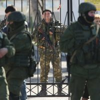 An armed Ukrainian soldier stands inside the gate of a Ukrainian military base as unidentified heavily-armed soldiers stand outside in Crimea on March 3, 2014 in Perevalne, Ukraine. (Sean Gallup/Getty Images)