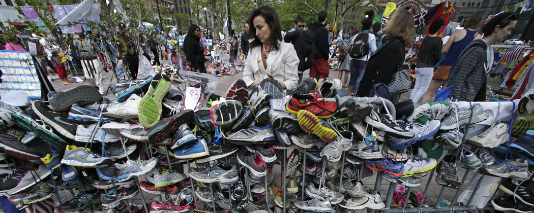 Denise White, of Duxbury,  pauses to read notes written on running shoes at the site of a memorial near the finish line of the Boston Marathon. (Charles Krupa/AP)