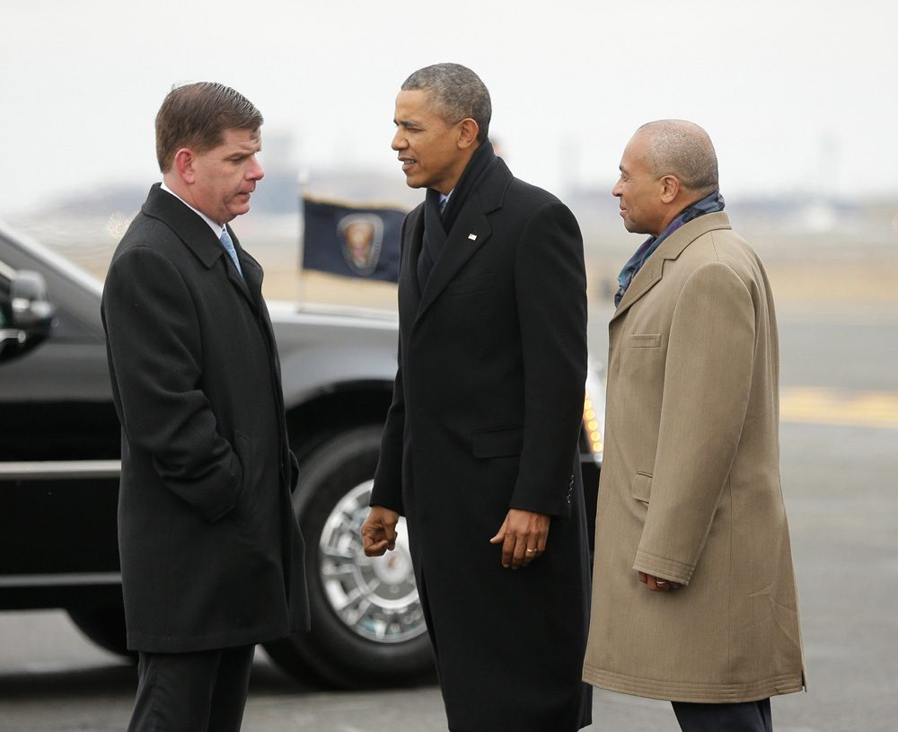 After his arrival at Logan Airport Wednesday afternoon, President Obama talks with Boston Mayor Mayor Martin Walsh, as Gov. Deval Patrick looks on. (Pablo Martinez Monsivais/AP)