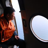 This picture taken aboard a Vietnamese Air Force Russian-made MI-171 helicopter shows a crew member looking out from a door during a search flight some 200 km over the southern Vietnamese waters off Vietnam's island Phu Quoc on March 11, 2014 as part of efforts aimed at finding traces of the missing Malaysia Airlines MH370. (Hoang Dinh Nam/AFP/Getty Images)