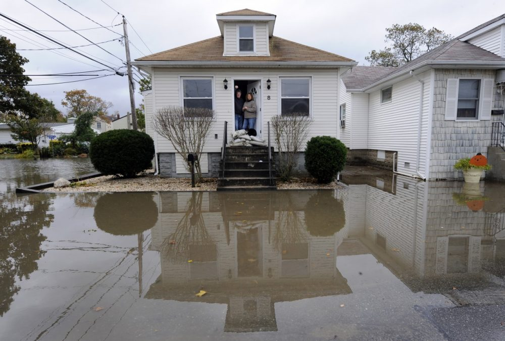 Anthony and Paula Bacco with their cat, Phoebe pose for a photogaph in their doorway barricaded with sand bags for protection against flooding from Hurricane Sandy. (Kathy Kmonicek/AP)