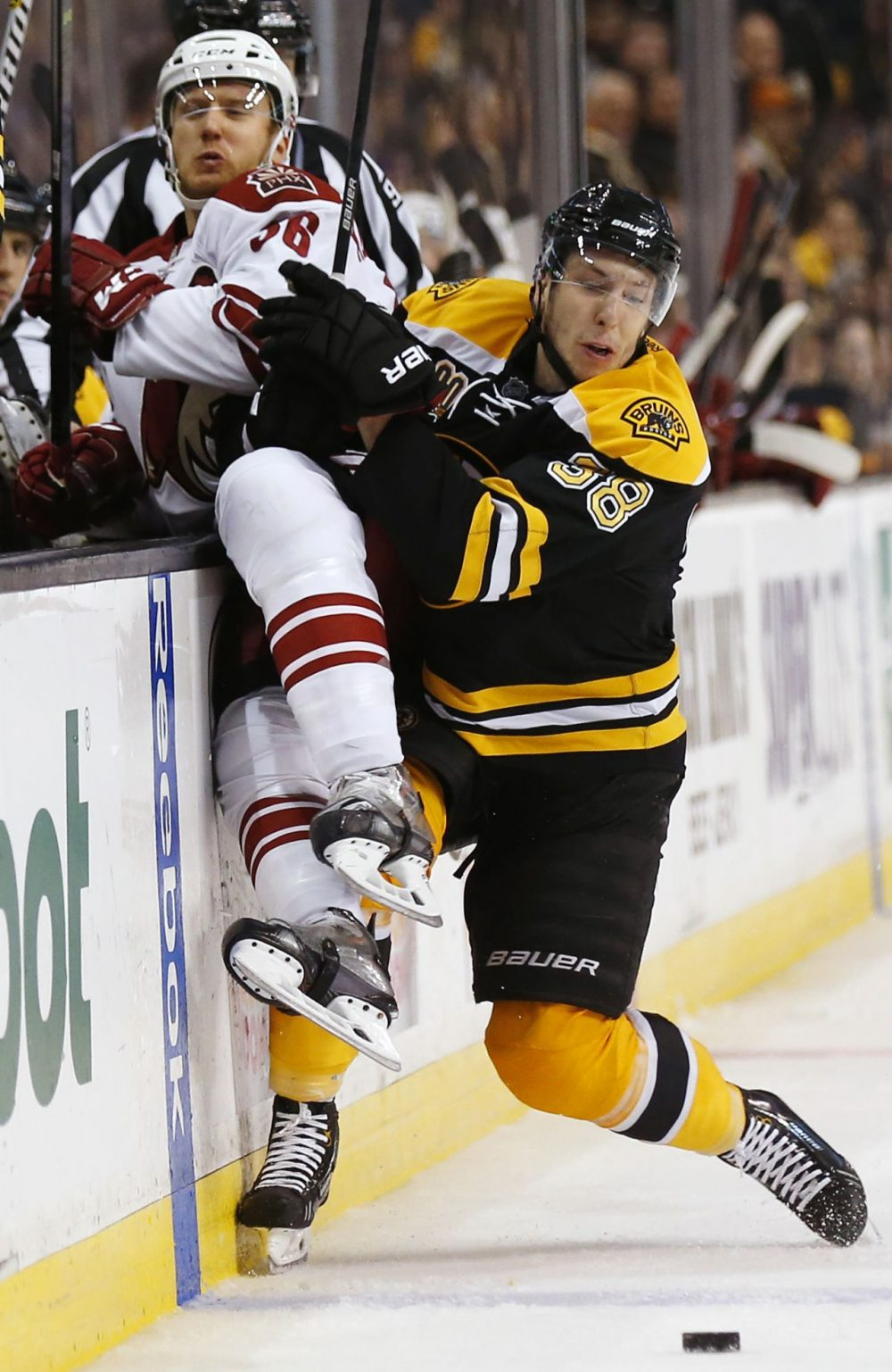 Boston Bruins' Jordan Caron checks Phoenix Coyotes' Rob Klinkhammer into the boards during the third period of Boston's 2-1 win in an NHL hockey game in Boston Thursday, March 13, 2014. (Winslow Townson/AP)