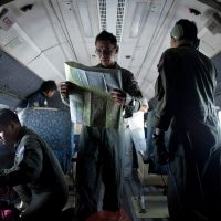 A Royal Malaysian Air Force Navigator captain, Izam Fareq Hassan, looks at a map onboard a Malaysian Air Force aircraft during a search and rescue operation to find the missing Malaysia Airlines flight MH370 plane, over the Strait of Malacca on March 14, 2014.  (Mohd Rasfan/AFP/Getty Images)