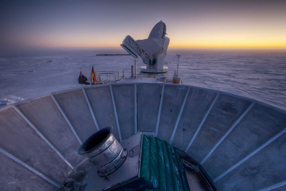 In this 2007 photo, the sun sets behind the BICEP2 telescope, foreground, and the South Pole Telescope in Antarctica. (Steffen Richter/AP)
