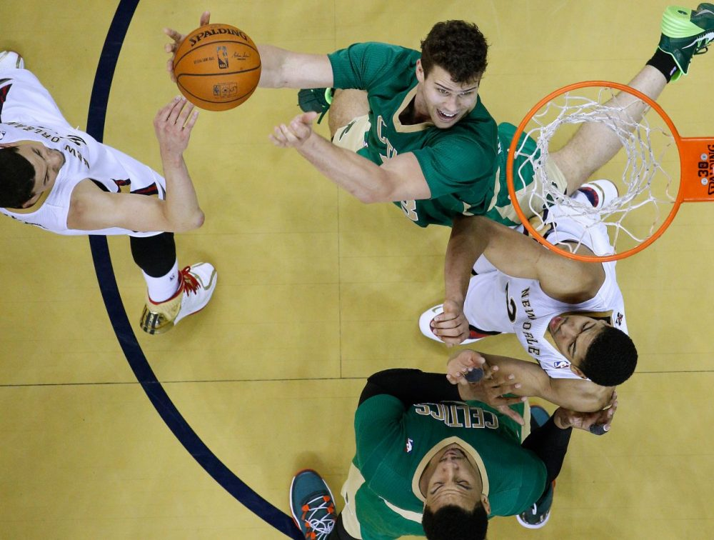Boston Celtics center Kris Humphries, top, goes to the basket against Pelicans forward Anthony Davis, right, and  guard Austin Rivers, left. (Jonathan Bachman/AP)