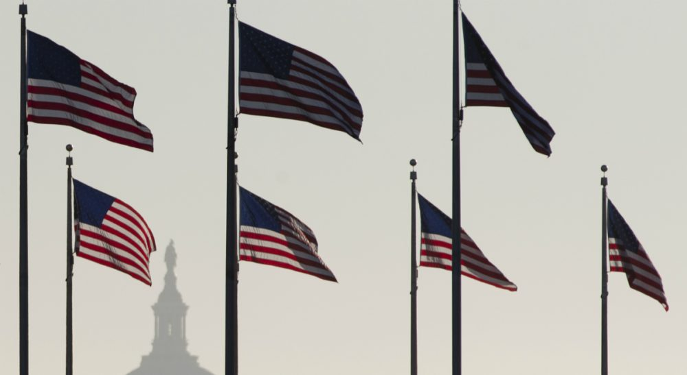 The U.S. Capitol Dome is seen in the distance as American flags fly on the National Mall around the base of the Washington Monument, Tuesday, Oct. 15, 2013, in Washington. (Carolyn Kaster/AP)