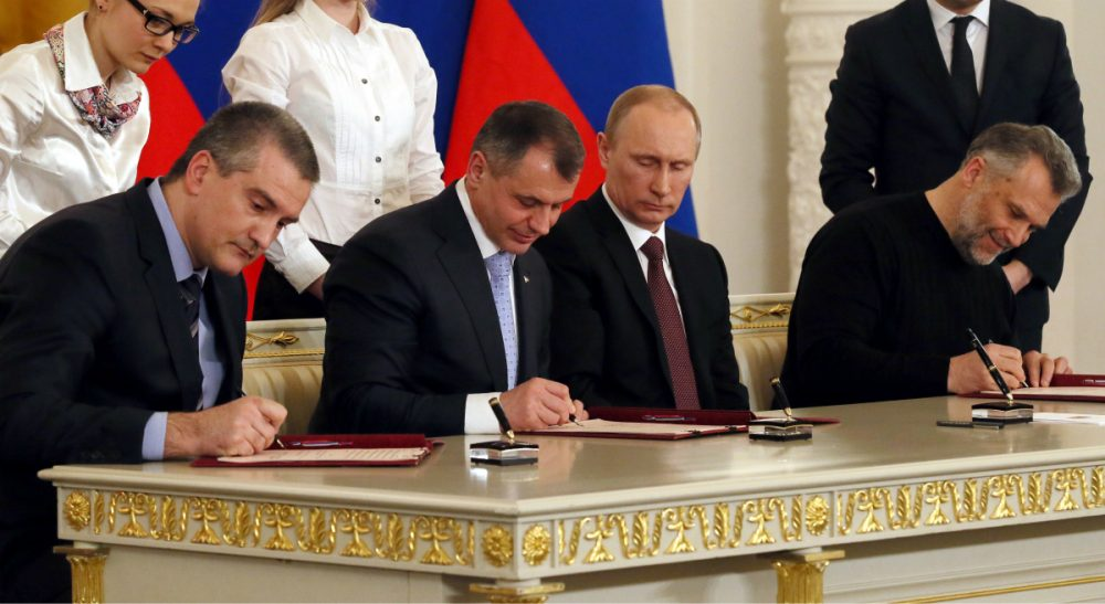 Russian President Vladimir Putin, second right, looks on as Crimean leaders sign a treaty for Crimea to join Russia in the Kremlin in Moscow, Tuesday, March 18, 2014. On the same day, Putin signed a treaty to incorporate Crimea into Russia, describing the move as the restoration of historic injustice and a necessary response to what he called the Western encroachment on Russia's vital interests. (Sergei Ilnitsky/AP)