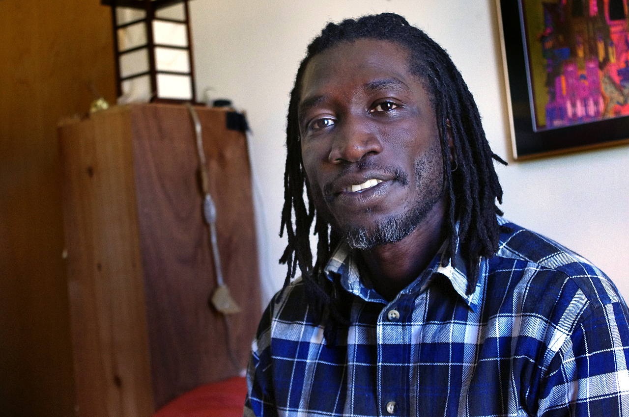 John Abdallah Wambere sits in his Cambridge apartment. (Gabrielle Emanuel/WBUR)