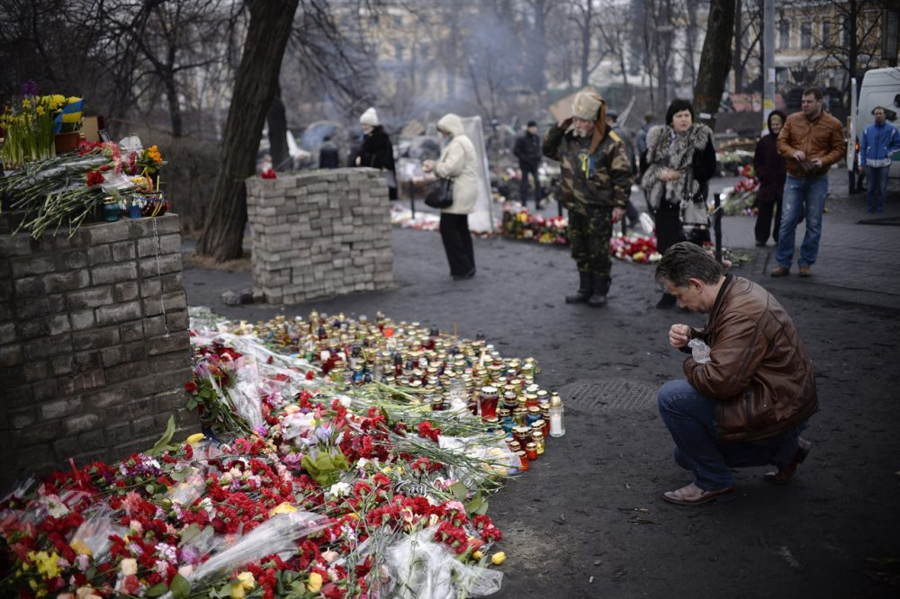 People pay their respects at a makeshift memorial where a protester was killed during clashes with police near Independence Square  The Ukrainian government has promised justice for the fallen, but citizens in Kiev remain uneasy. (Dimitar Dilkoff/AFP/Getty Images)