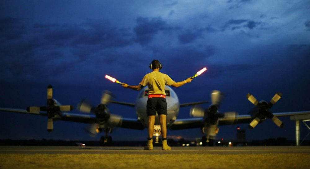 A ground controller guides a Royal Australian Air Force AP-3C Orion to rest after sunset upon its return from a search for the missing Malaysia Airlines flight MH370 over the Indian Ocean, at the Royal Australian Air Force base Pearce in Perth, Monday, March 24, 2014. New analysis of satellite data indicates the missing plane crashed into a remote corner of the Indian Ocean. (Jason Reed/AP)