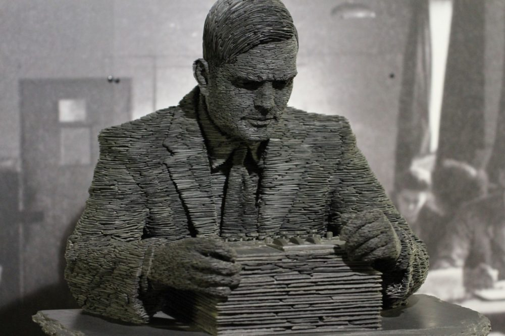 A statue of Alan Turing at the Bletchley Park Museum, poring over an Enigma machine. (Duane Wessels/Flickr)