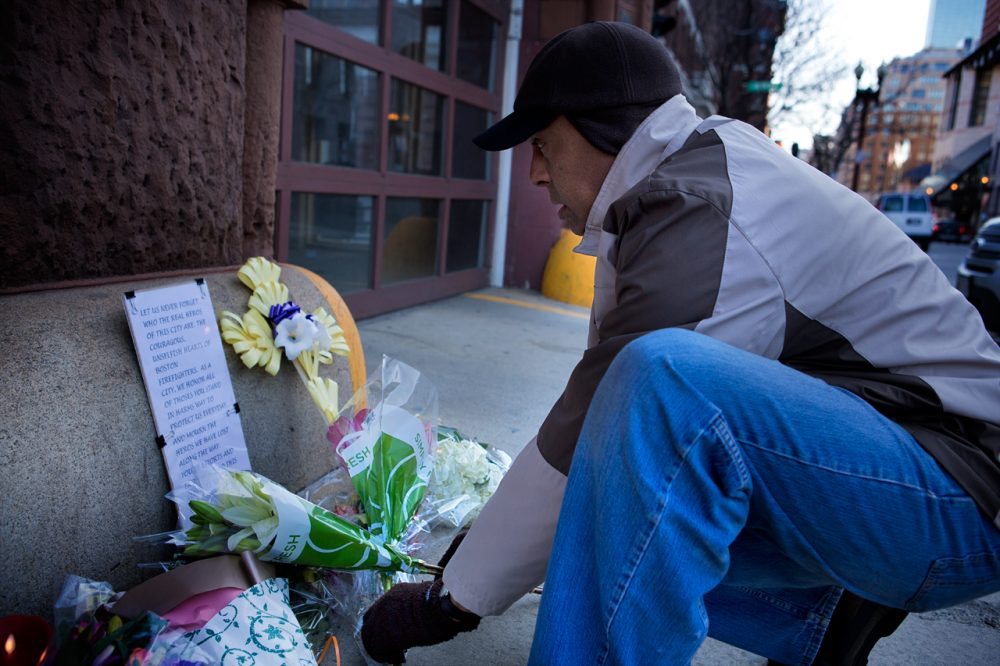 Michael Morrison, who's up from Martha's Vineyard getting cancer treatment in Boston, visits a makeshift memorial at the Engine 33 fire station on Thursday. Engine 33 was the station of fallen firefighters Lt. Edward Walsh and Michael Kennedy.