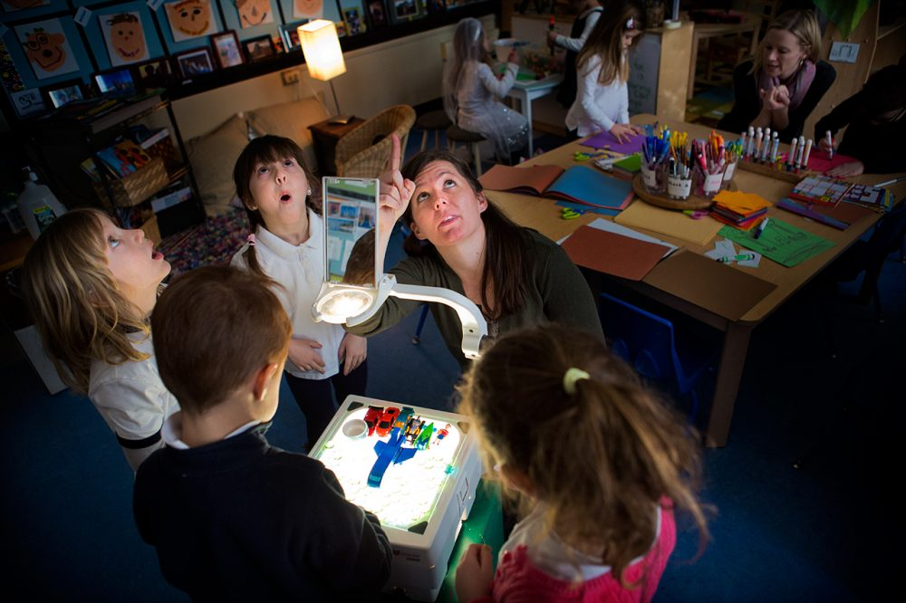 Using a projector, Jodi Doyle points out shadows on the ceiling to students of her preschool class at the Eliot K-8 Innovation School in Boston's North End. (Jesse Costa/WBUR)
