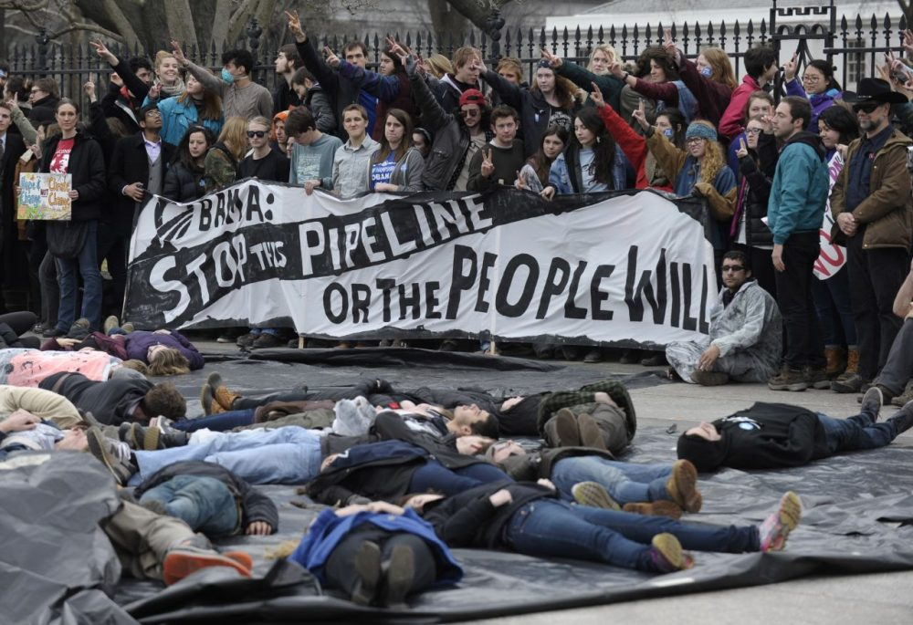 Several hundred students and youth who marched from Georgetown University to the White House to protest the Keystone XL Pipeline wait to be arrested outside the White House in Washington, Sunday, March 2, 2014. (Susan Walsh/AP)