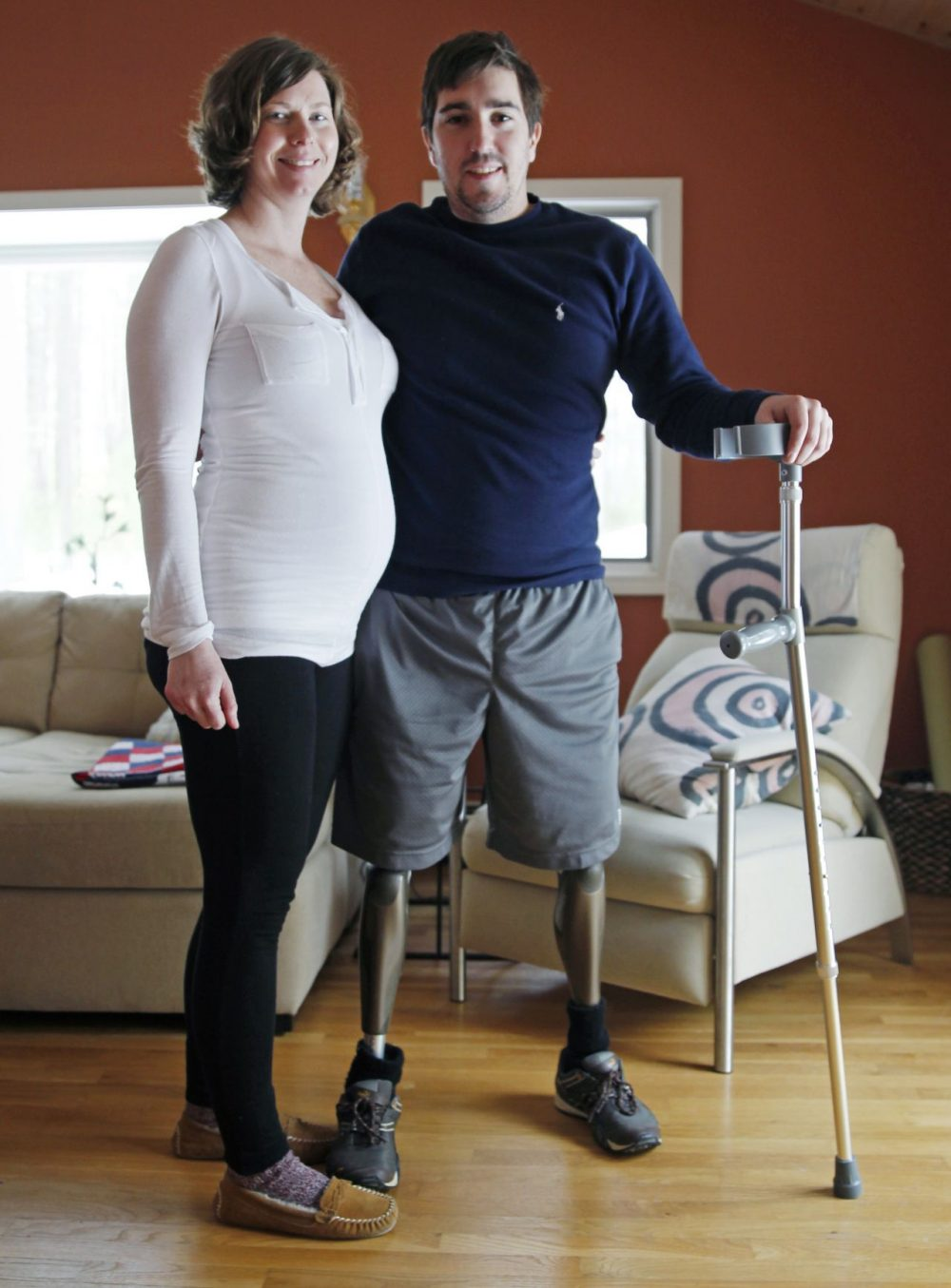 Jeff Bauman, who lost both legs in the Boston Marathon bombings, then helped authorities identify the suspects, poses with his expectant fiancé, Erin Hurley, their home in Carlisle, Mass., Friday, March 14, 2014. According to Bauman, the baby is due July 14. They don't know if it's a boy or a girl, and they want it to be a surprise. The two were engaged in February. (Charles Krupa/AP)