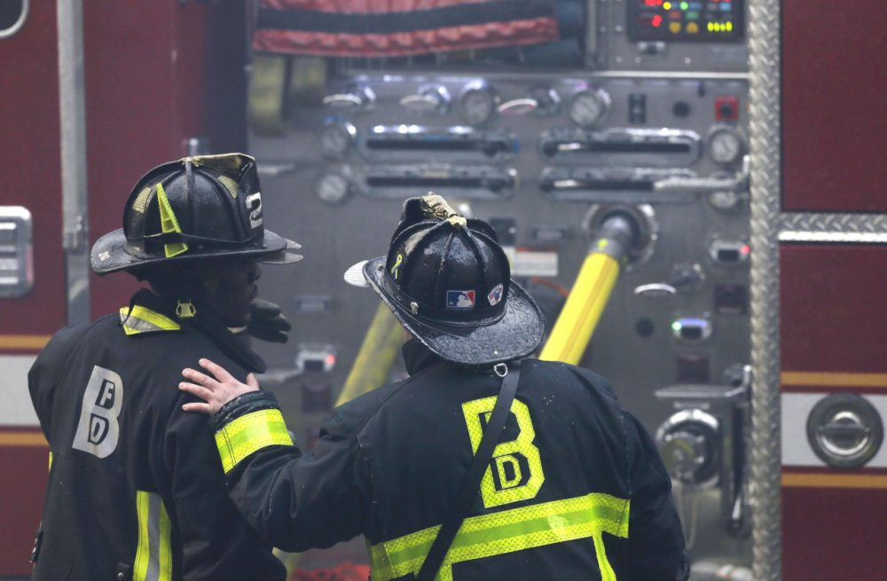 A firefighter places his hand on the shoulder of another at the scene of a multi-alarm fire at a four-story brownstone in the Back Bay neighborhood near the Charles River, Wednesday, March 26, 2014 in Boston. (AP)