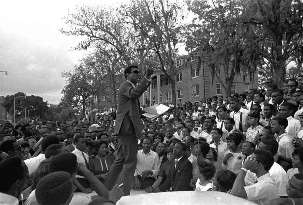 "Stokely Carmichael, national head of the Student Nonviolent Coordinating Committee speaks from the hood of an automobile on the campus of Florida A&M University, April 16, 1967, in Tallahassee, Florida. Several hundred students listened as Carmichael spoke of ""Black Power"" and the Vietnam war. (AP)"