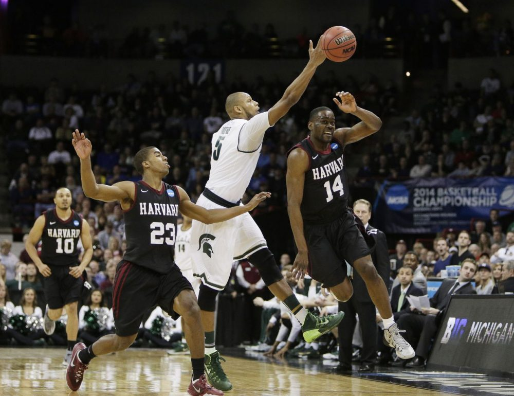 Michigan State's Adreian Payne (5) fights for a loose ball against Harvard's Wesley Saunders (23) and Steve Moundou-Missi (14) during the third-round game of the NCAA men's college basketball tournament in Spokane, Wash., Saturday, March 22, 2014. (Young Kwak/AP)
