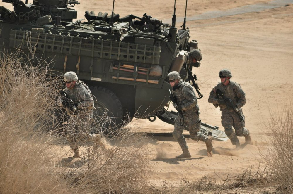 US Army troops run out of a Stryker armored vehicle as part of a military exercise. (AP/Dinesh Gupta)