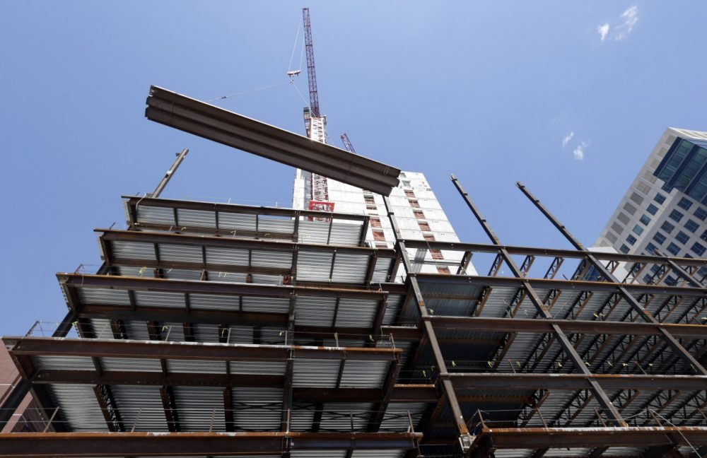 A large beam is lifted by a crane at a construction site in Boston. (AP/Elise Amendola)