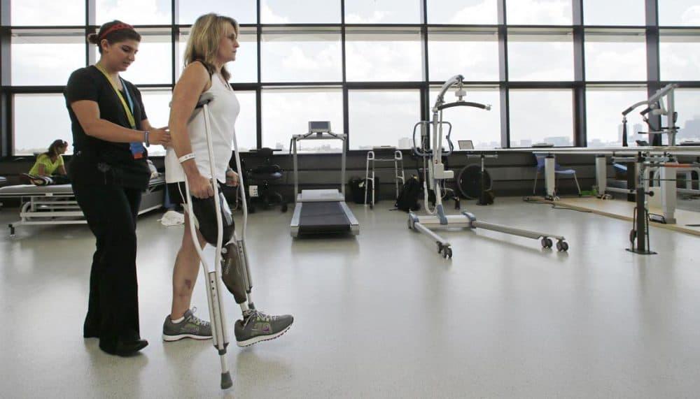 Physical therapist Dara Casparian, left, guides Boston Marathon bombing survivor Roseann Sdoia at the Spaulding Rehabilitation Hospital in June. (Charles Krupa/AP)