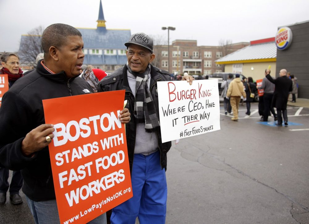 Pedro Rodriguez, right, and Andrus Reyes participate in a demonstration on a Burger King parking lot as part of a nationwide protest supporting higher wages for workers in the fast-food industry and other minimum wage jobs in Boston, Dec. 5, 2013. (AP/Stephan Savoia)