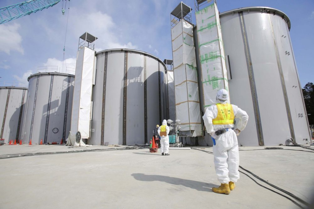 A worker in a protective suit and a mask looks at tanks, under construction, to store radioactive water, in the J1 area at the Tokyo Electric Power Co's (TEPCO) tsunami-crippled Fukushima Dai-ichi nuclear power plant in Okuma, Fukushima prefecture, northeastern Japan, Monday, March 10, 2014. (AP)